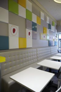 Noa: bespoke fixed soft seating with yellow buttons